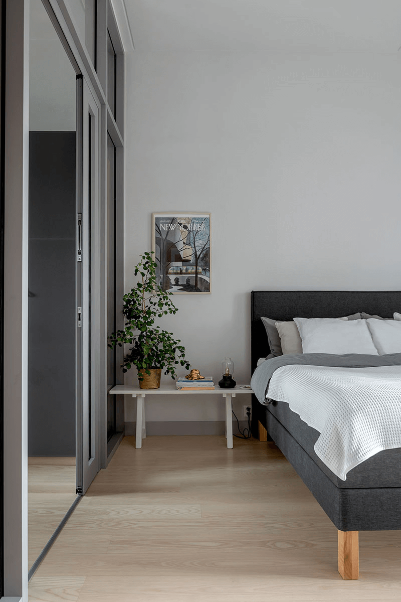 this is a Scandinavian bedroom with a simple double bed and art on the wall in a grey accent feel
