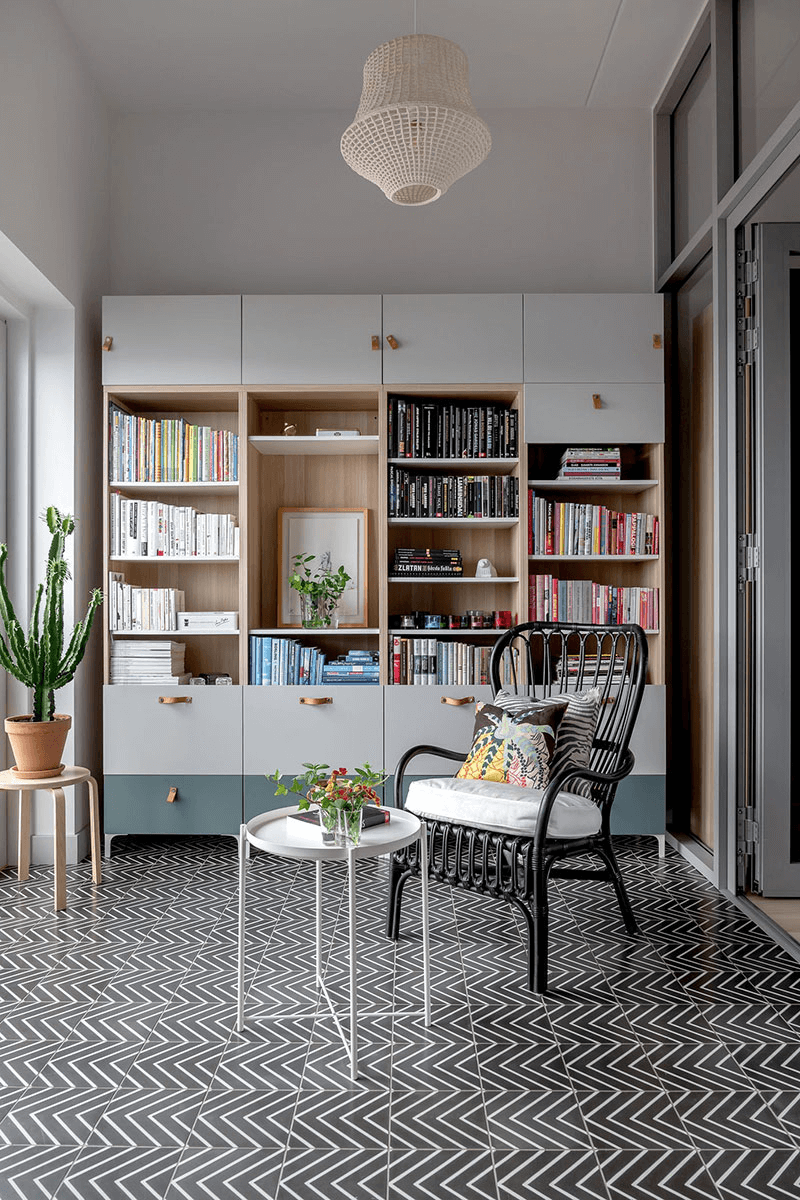 this is a classic Scandinavian room with wooden cabinets, a chair with a cushion and house plants