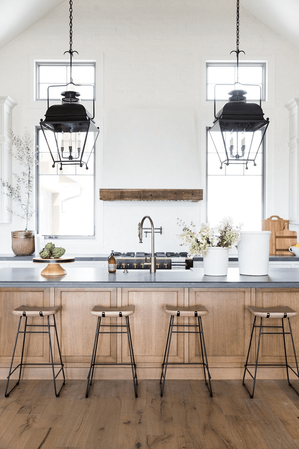this is a farmhouse kitchen with a rustic feel and counter stools and sleek surface(1)