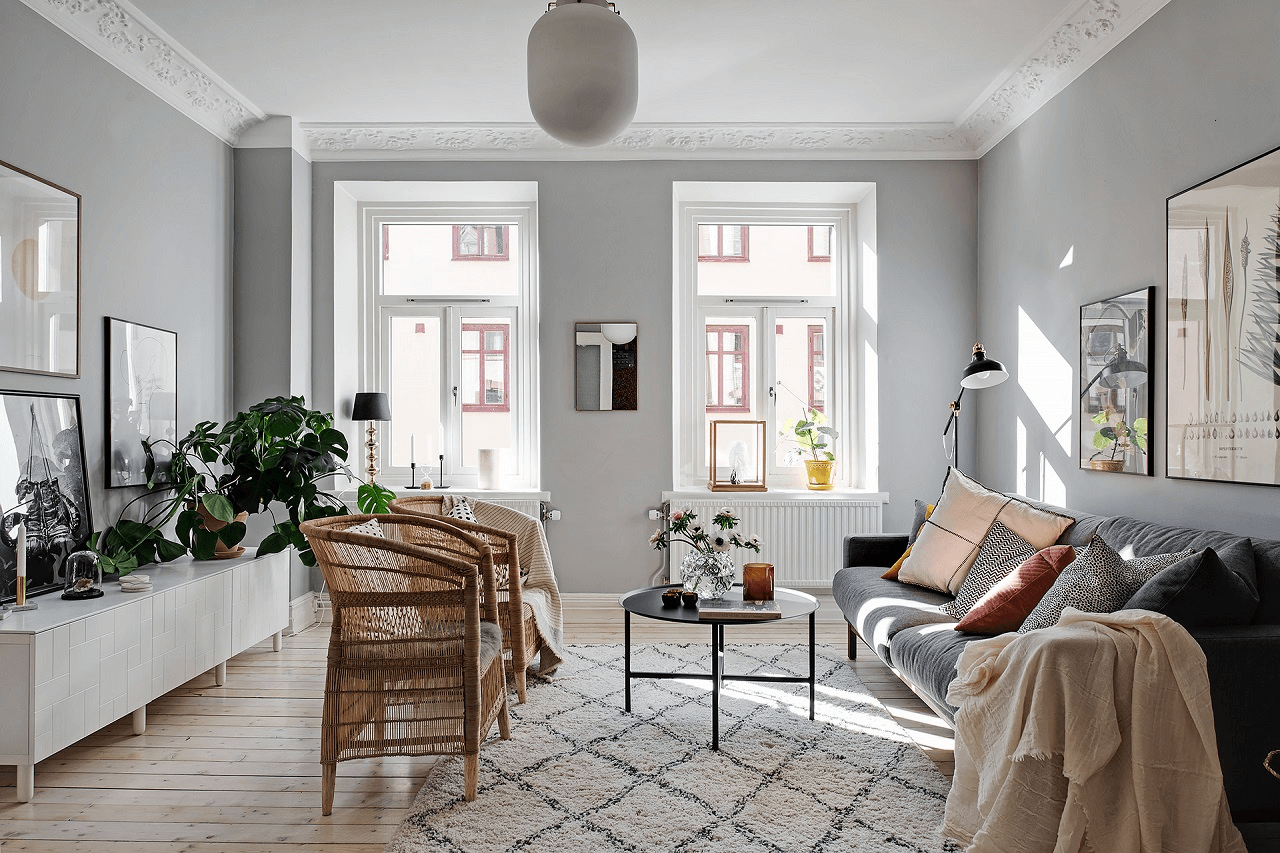 this is a look into a scandinavian living room with light entering through large windows and many rugs and throws on the sofa with plants surrounding