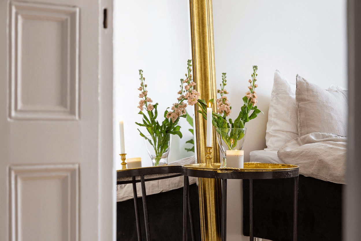 this is a minimal Scandinavian styled apartment with a focus on the metal side table and mirror