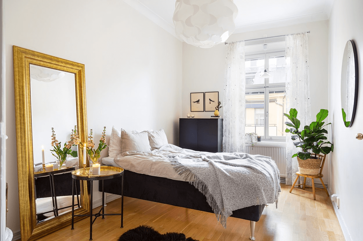 this is a minimal Scandinavian styled bedroom with a large golden brass mirror, and double bed