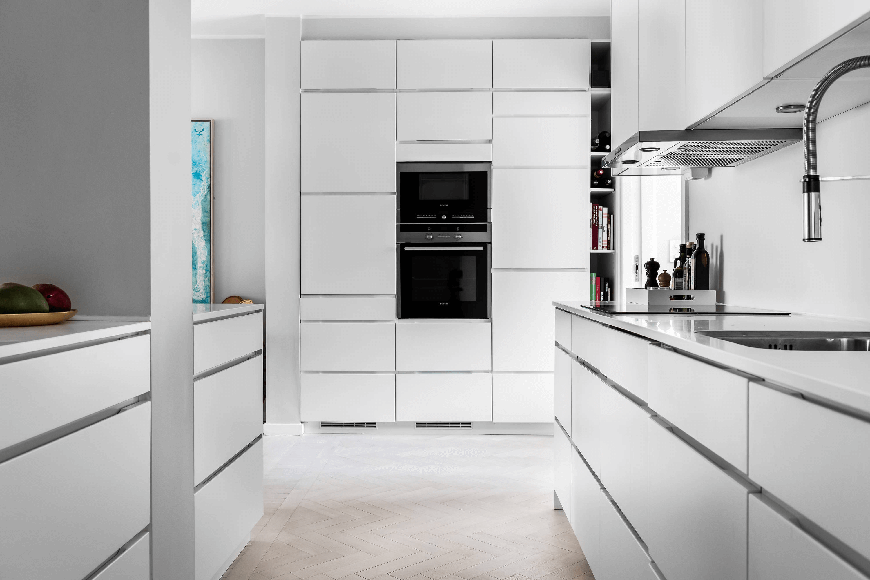 this is a modern scandinavian kitchen with white fixtures, clean lines and minimal objects on surfaces