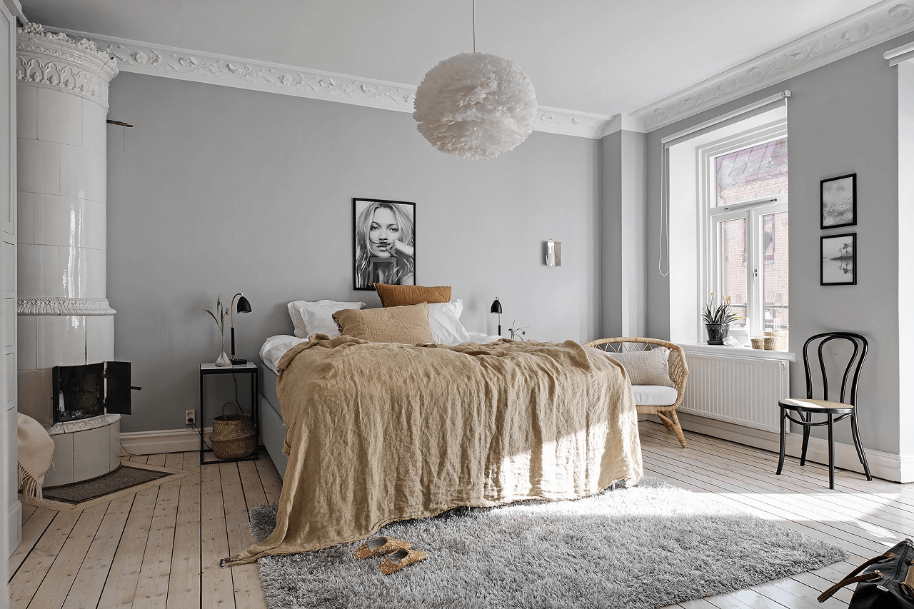 this is a relaxed bedroom with art, wooden floors, lots of light and a fireplace next to the double bed