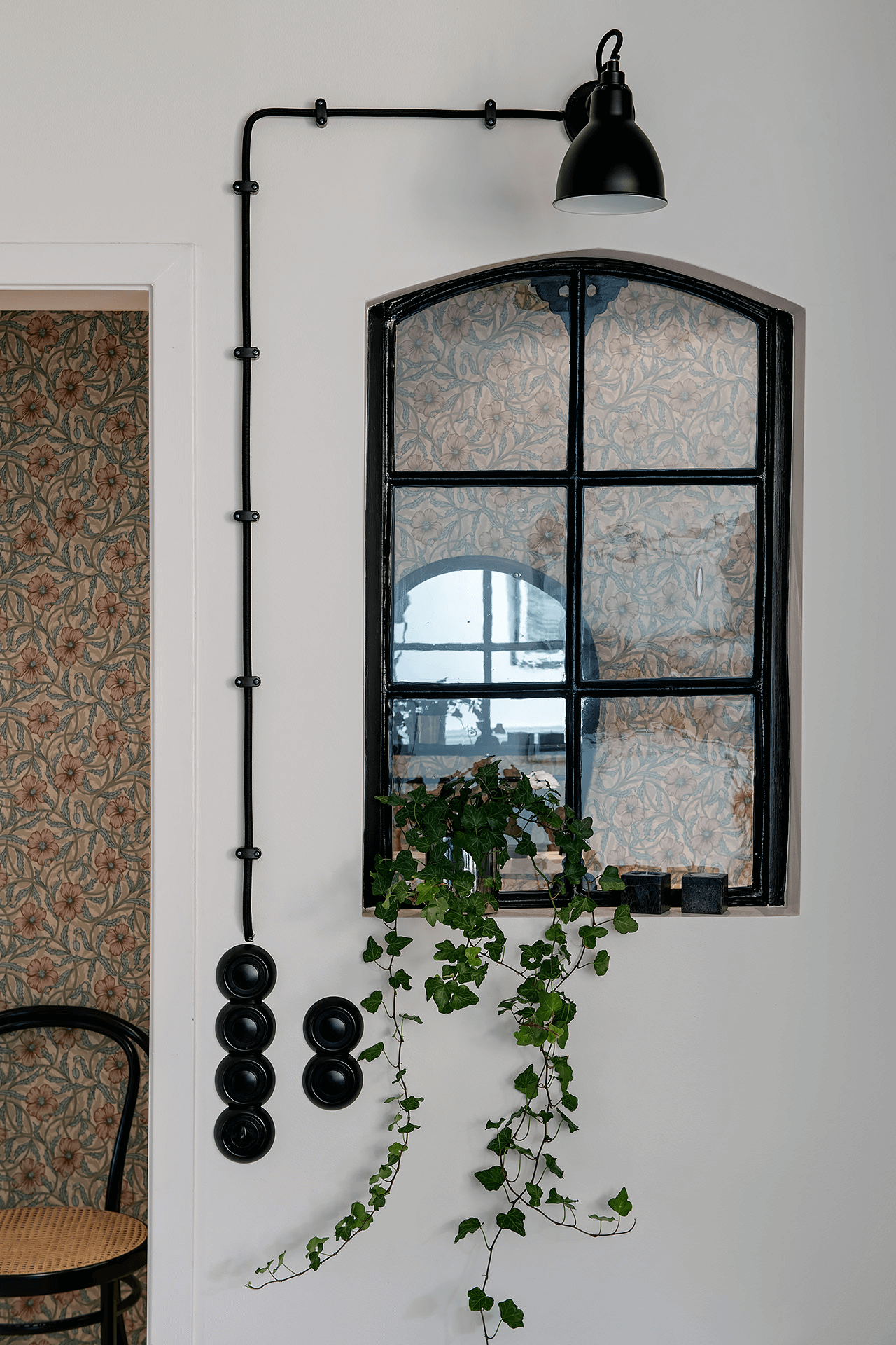 this is a window in an scandinavian styled apartment with a lamp shade and indoor plants surrounding it