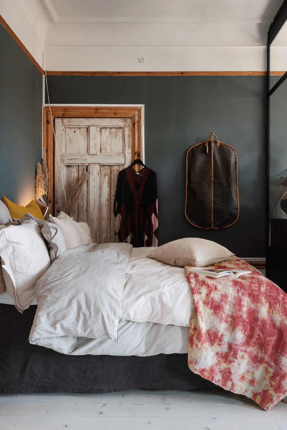 this is a wooden styled Scandinavian apartment with a bedroom that has clothes hanging and textured bedding