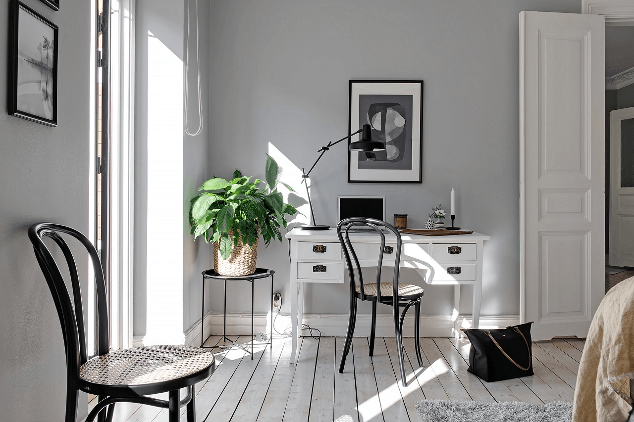 this is an office room in a scandinavian styled apartment with white office furniture, wooden floors and grey walls