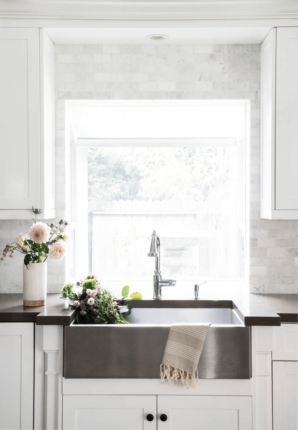 this is an stainless steel apron sink in a farmhouse kitchen