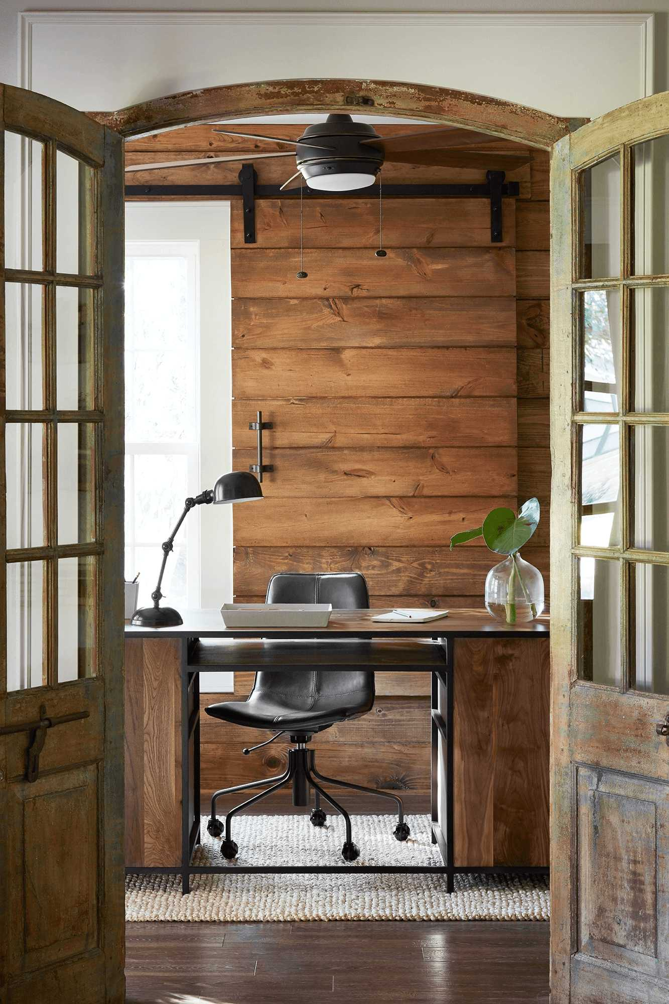 this-is-a-farmhouse-home-office-with-antique-doors-and-leather-chair-wooden-desk1