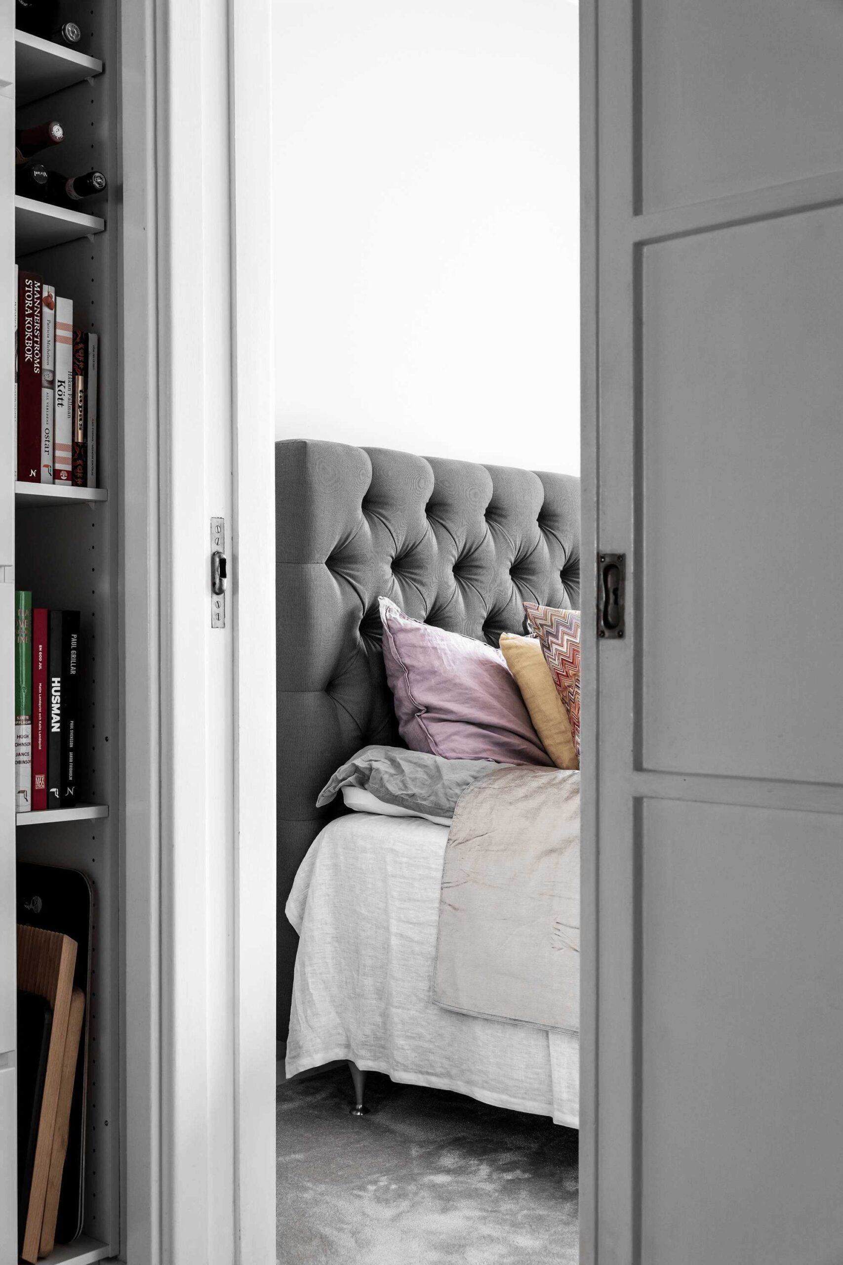 this-is-a-look-at-a-bed-in-a-scandinavian-apartment-with-a-bookshelf-on-the-side-to-show-the-small-initimate-space