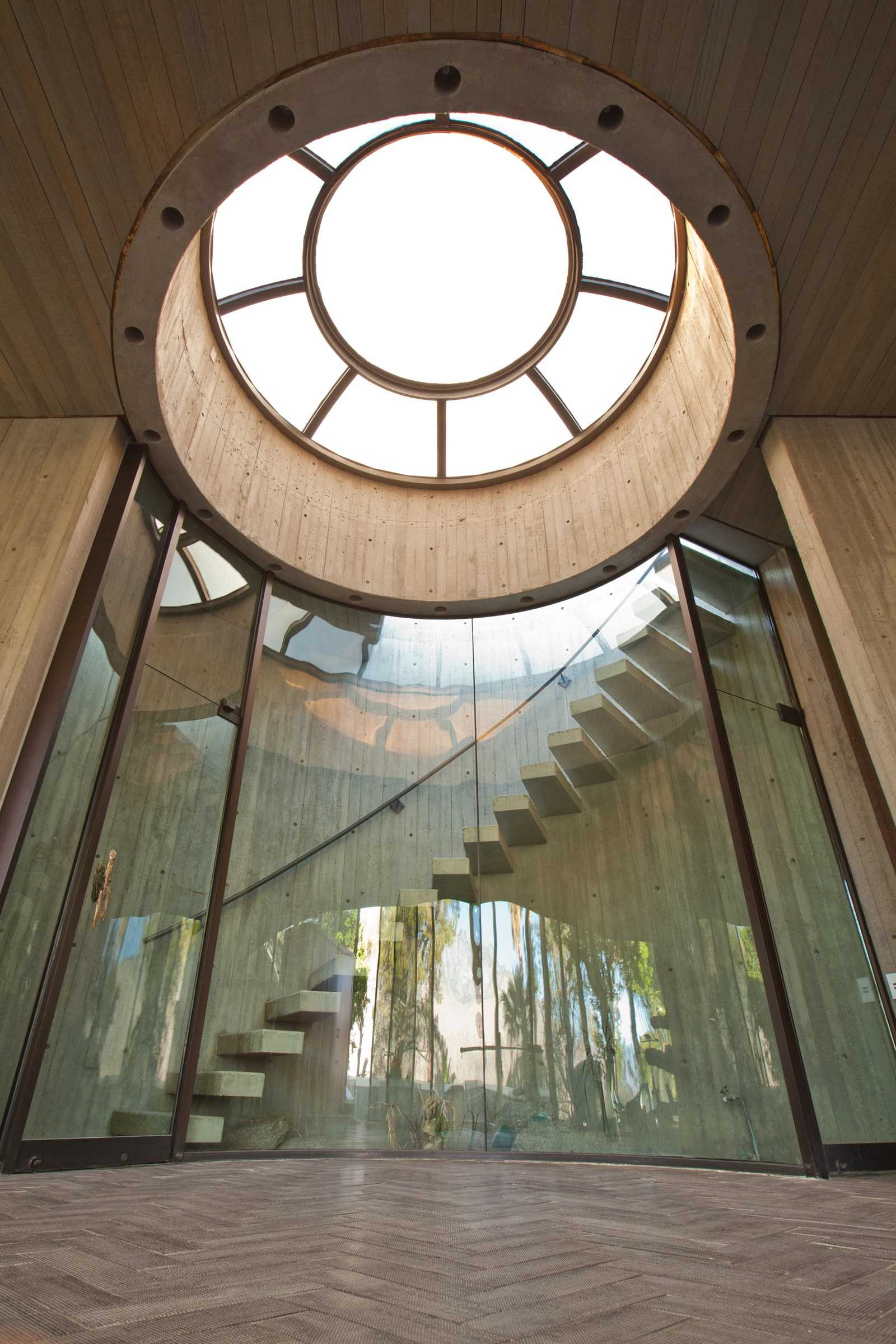 this-is-inside-the-Elrod-House-showing-the-grand-curves-of-the-home-and-a-view-of-the-floor-to-ceiling-glass-windows