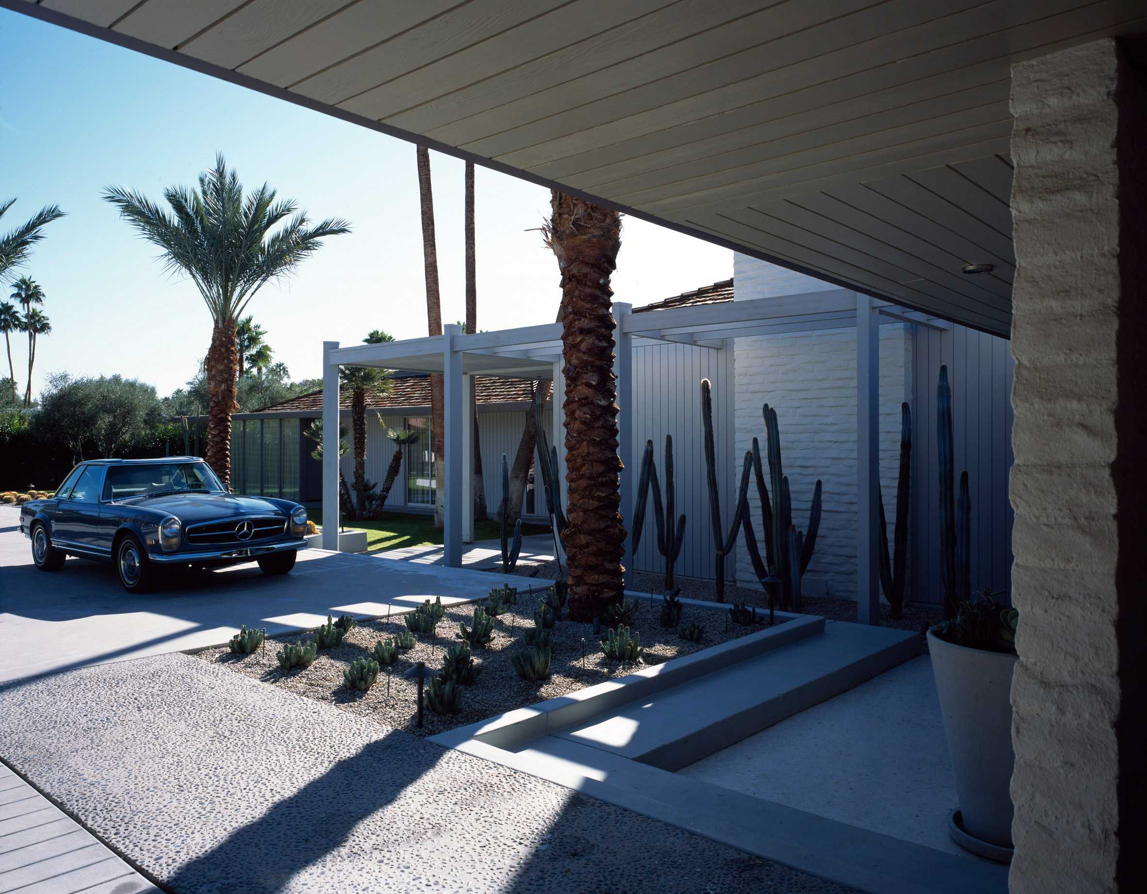 this-is-the-Abernathy-Residence-located-in-Palm-Springs-showing-a-car-parked-outside-surrounded-by-palm-trees-and-cactus