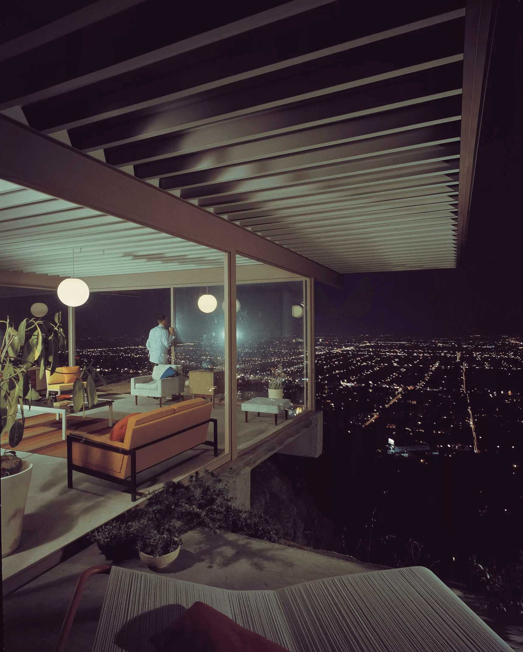 this-is-the-Stahl-House-in-West-Hollywood-showing-a-night-view-of-LA-with-a-look-into-the-living-room-with-floor-to-ceiling-windows-on-show-as-well-as-the-furniture