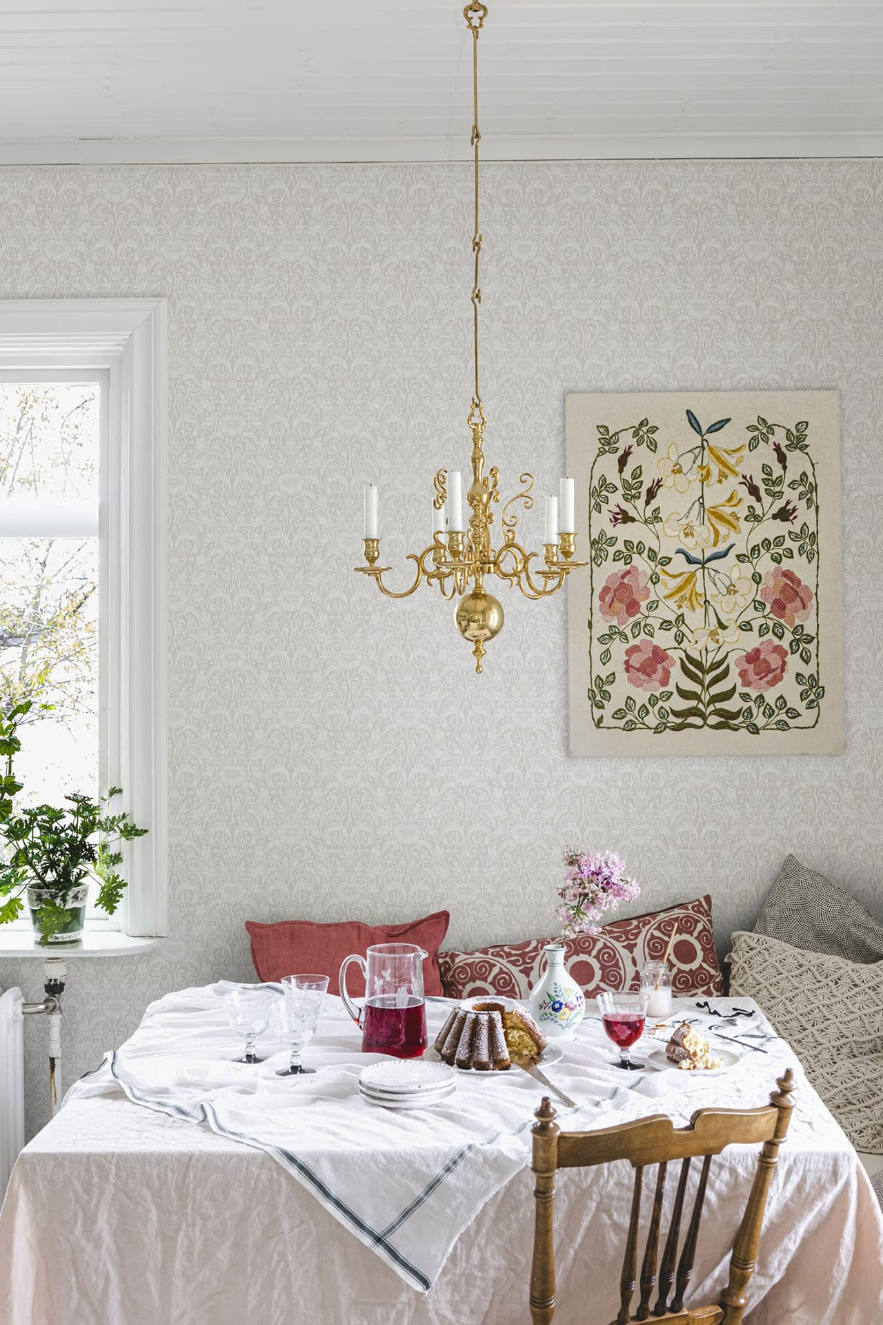 this is a dining room with light floral motif wallpaper inspired by shabby chic