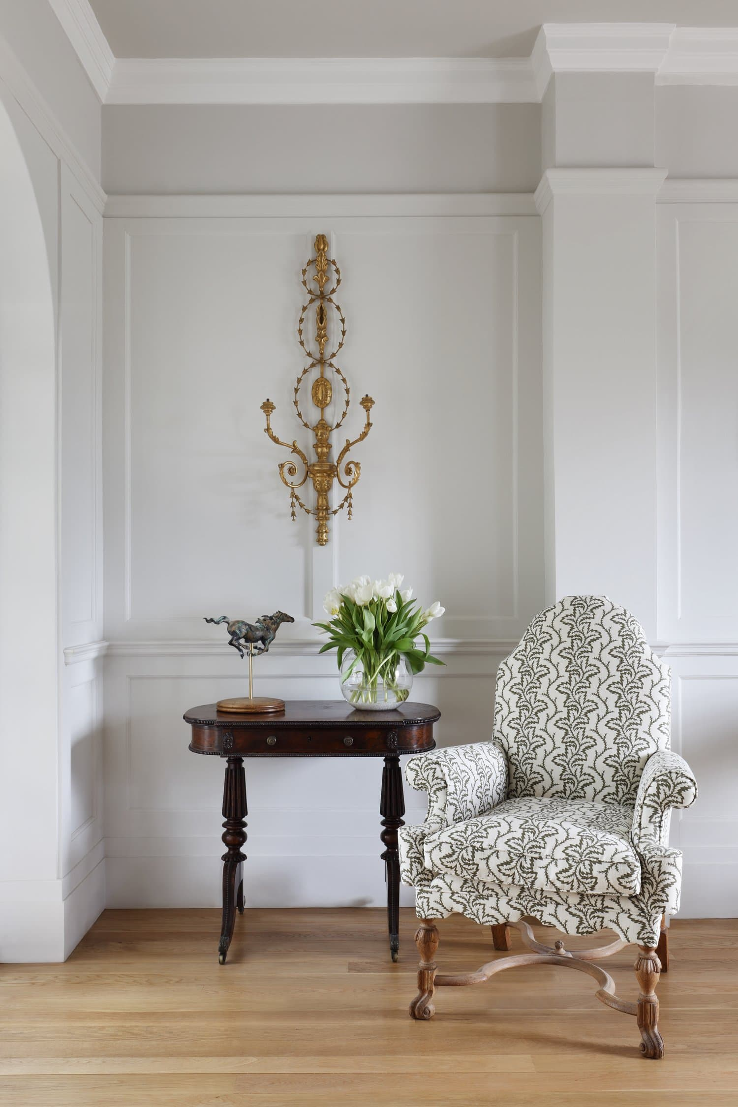 this is a hallway with a patterned chair and light grey walls