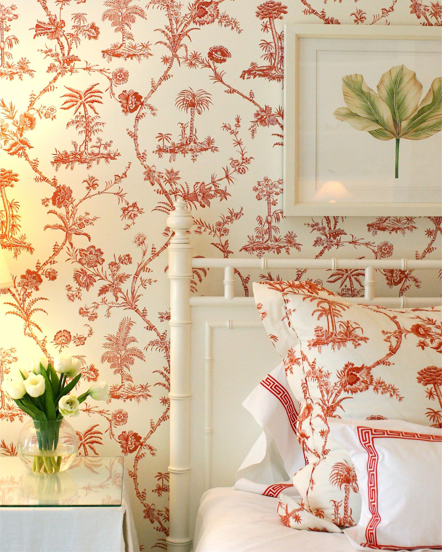 this is a red floral motif wallpaper in a bedroom with white elements