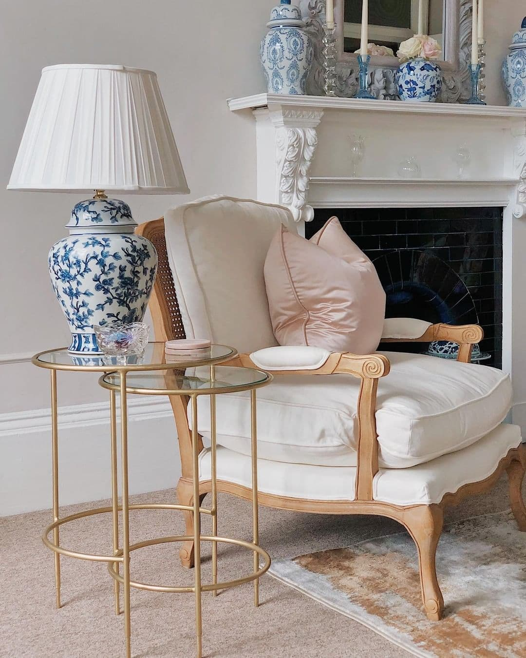 this is a shabby chic inspired armchair with a pink cushion and chinaware
