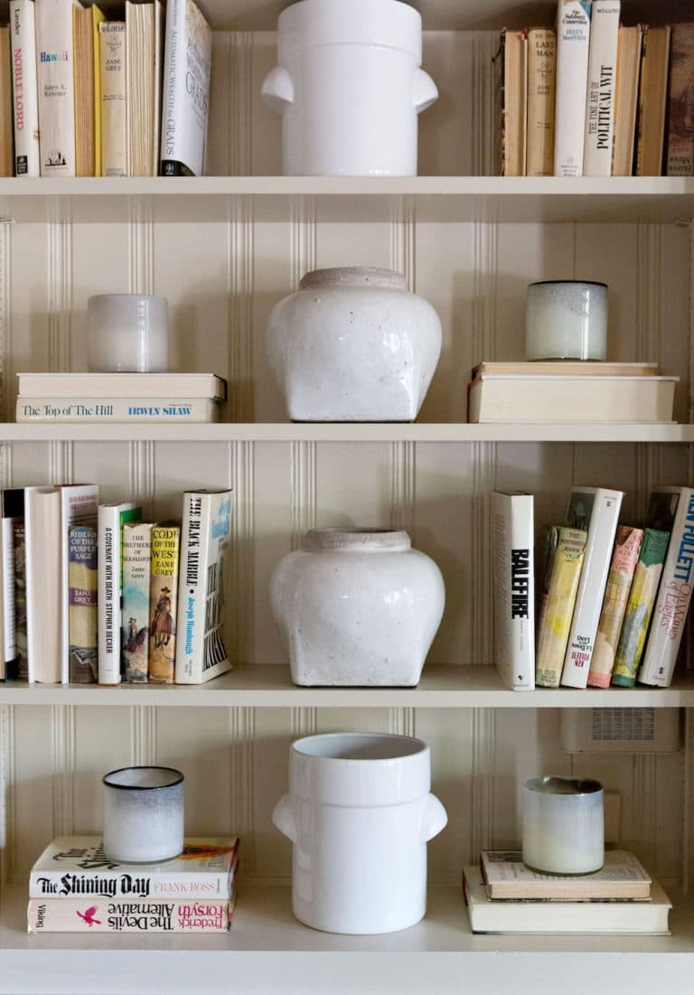 this is a bookcase with ceramics