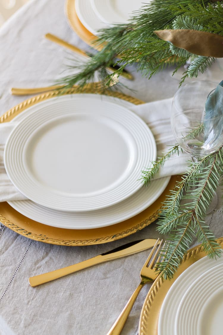 this is a christmas tablescape with terracotta place setting