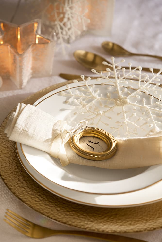 this is a pink and gold tablescape with a white place setting