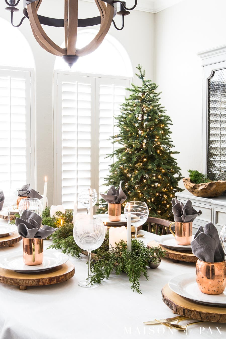 this is a white christmas tablescape with wooden place settings