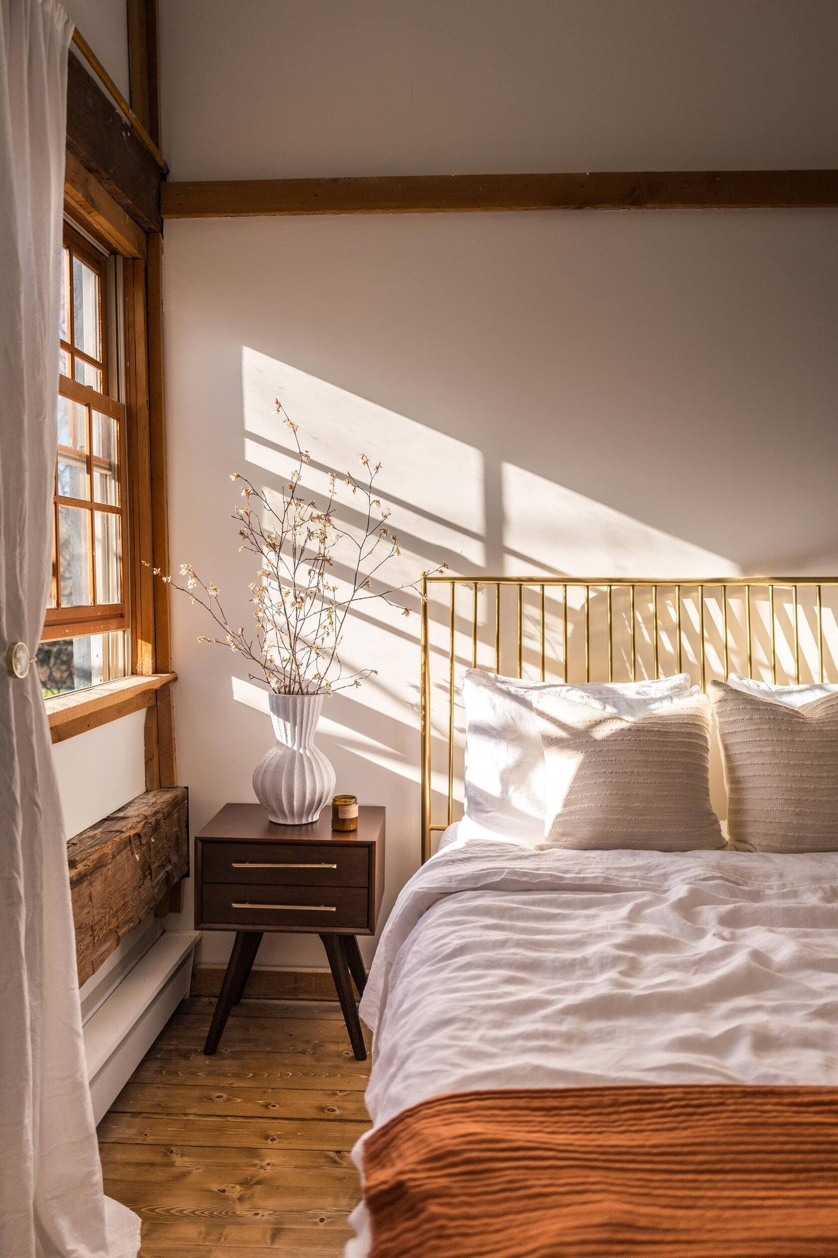 this is a bedroom with natural light shining through the window