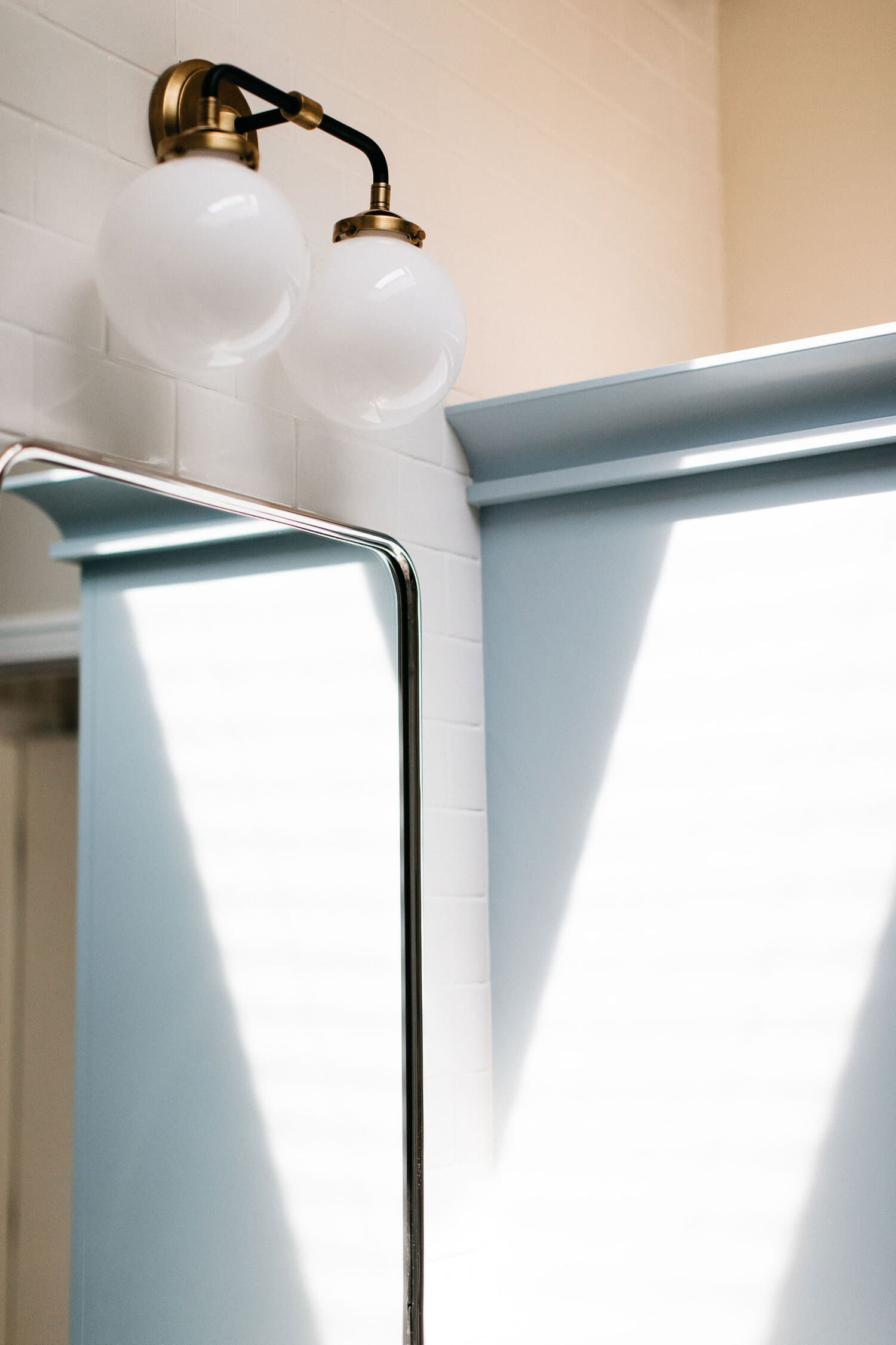 this is a bathroom with pale blue colours and brass elements