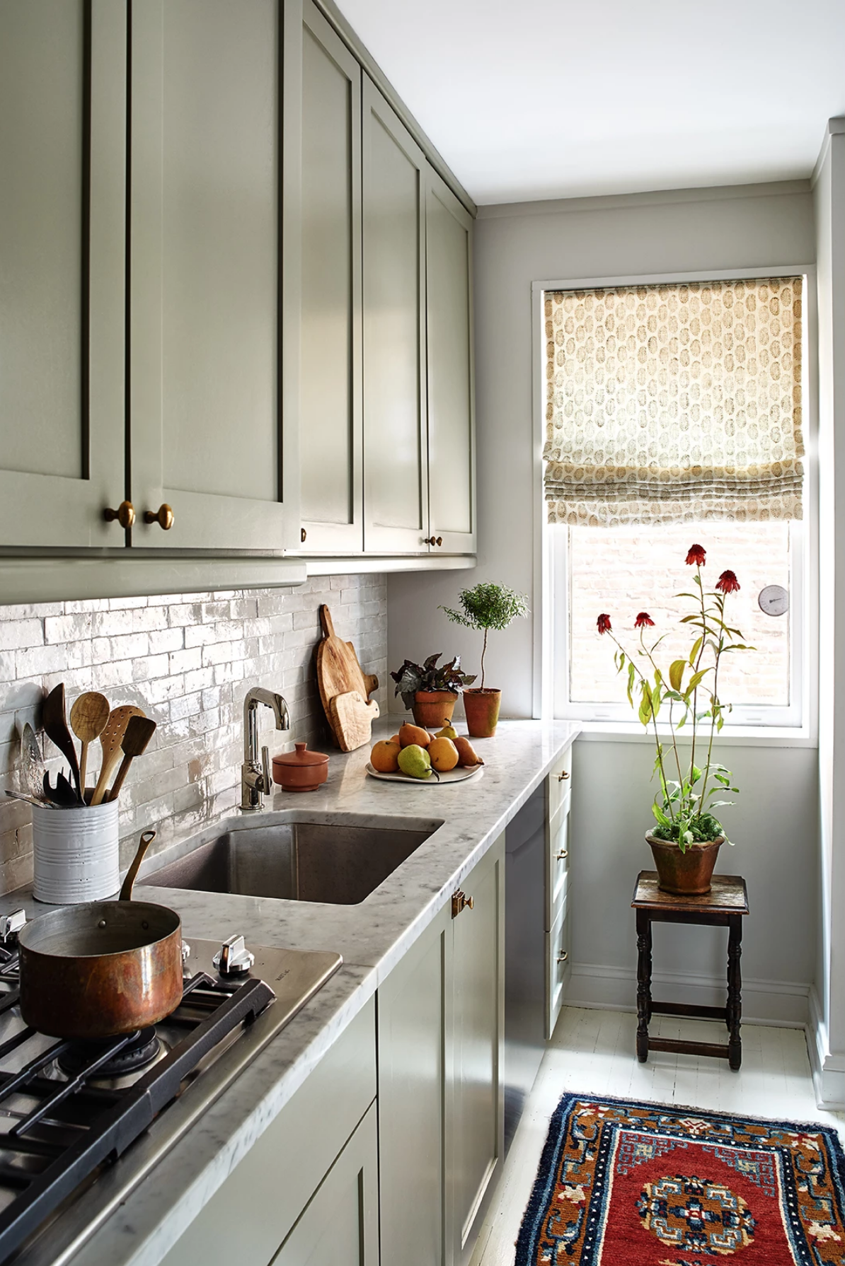 this is a small kitchen with light green cabinets