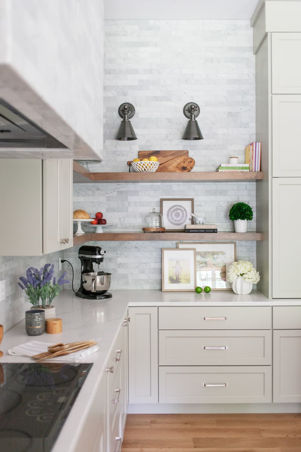 this is a spring inspired kitchen with light green cabinets and wooden shelves