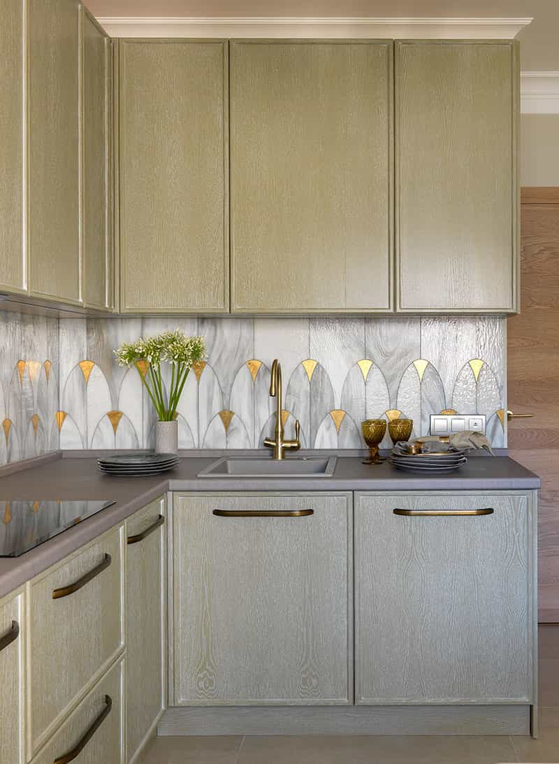 this is an art deco inspired kitchen with gold and silver tiles