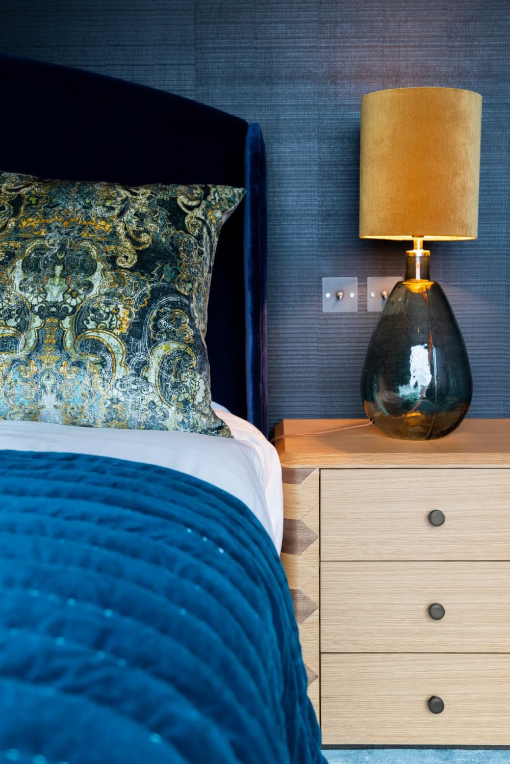 this is a dark bedroom with navy tiles and bed linen
